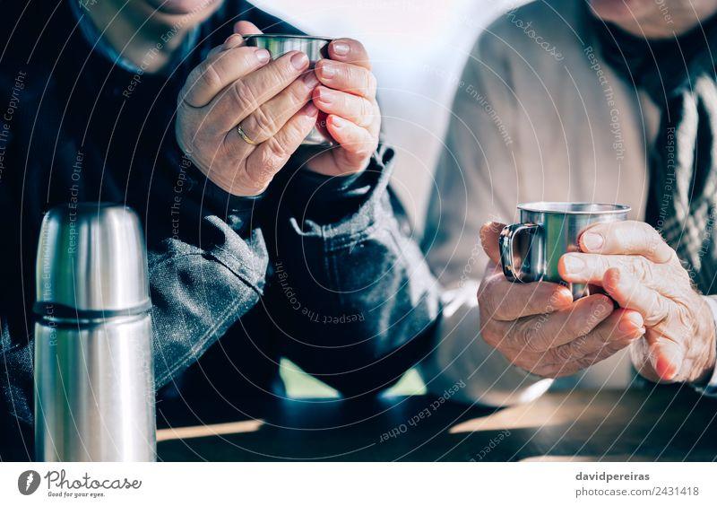 Senior Paar Hände halten Tassen mit heißem Kaffee. Tee Lifestyle Erholung Freizeit & Hobby Tisch Mensch Frau Erwachsene Mann Hand Wärme Holz Metall Liebe sitzen