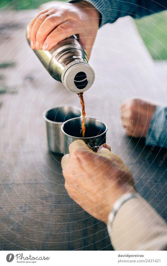 Senior Paar Hände gießen Kaffee aus der Thermoskanne. trinken Tee Lifestyle Erholung Freizeit & Hobby Tisch Mensch Frau Erwachsene Mann Hand Holz Metall alt