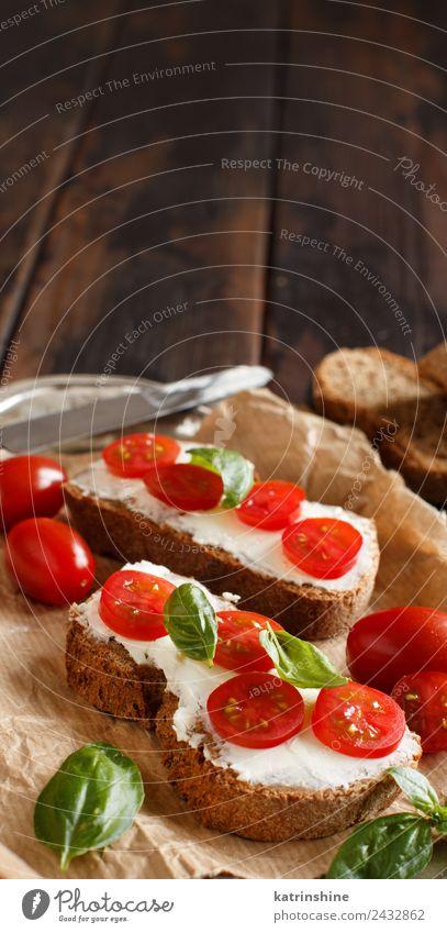 Bruschetta mit Frischkäse, Kirschtomaten und Basilikum Käse Brot Essen Frühstück Mittagessen frisch grün Amuse-Gueule Baguette Holzplatte Essen zubereiten Sahne