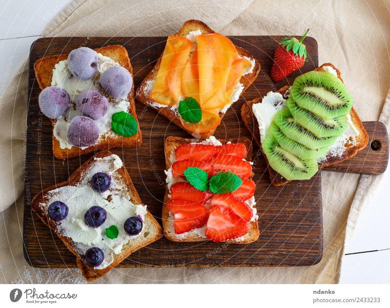 Französische Toasts mit Weichkäse Käse Frucht Brot Dessert Frühstück Holz Essen oben weich grün weiß Erdbeeren Zuprosten Kiwi Blaubeeren Molkerei Walnussholz