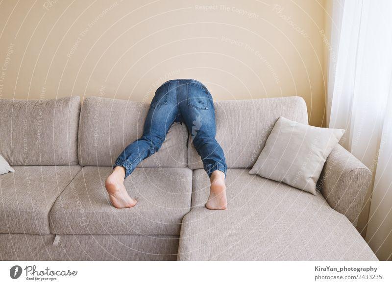 Der Mann in Jeans putzt hinter dem Sofa. Lifestyle Erholung Spielen Möbel Hooligan Erwachsene Vater Gesäß Fuß Bekleidung Jeanshose Traurigkeit Sauberkeit Stress