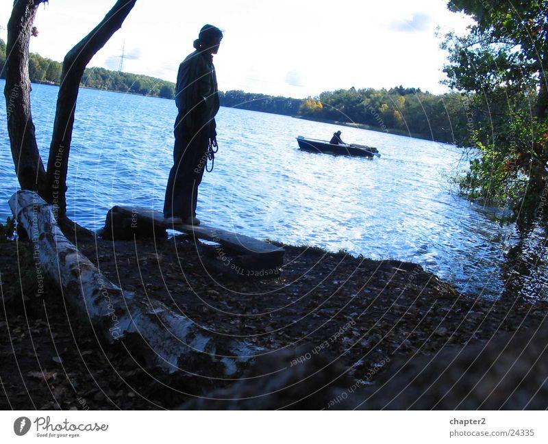 Frau am See Wasser Baum Wasserfahrzeug stehen