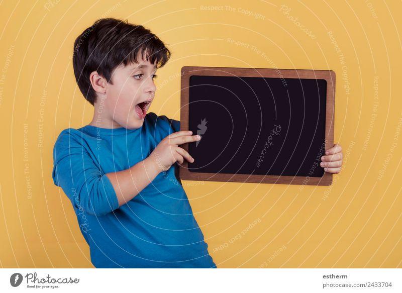 überraschter Junge mit einer Tafel Lifestyle Freude Bildung Kind Schule Mensch maskulin Kindheit 1 8-13 Jahre festhalten Fitness Lächeln Fröhlichkeit lustig