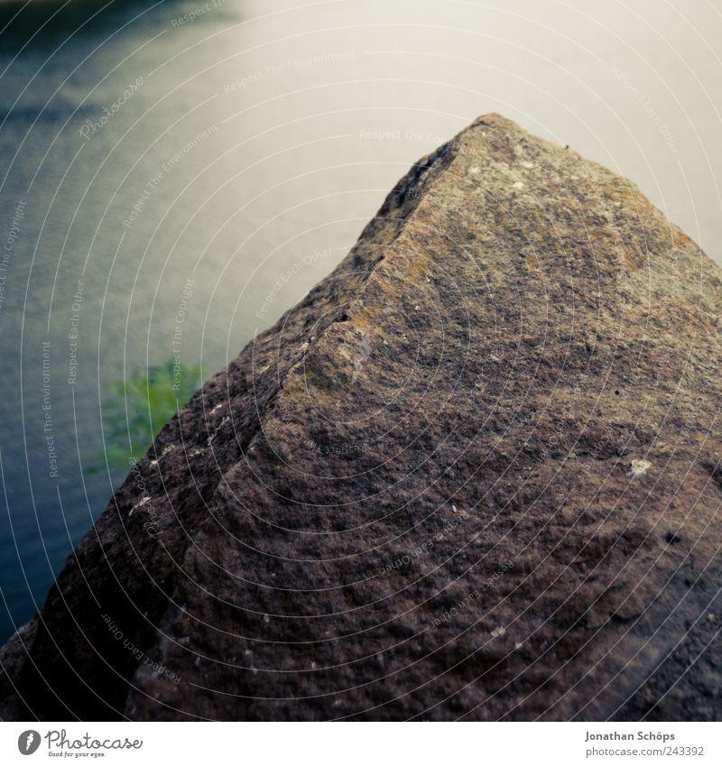 Der Felsen vor dem Wasser Umwelt Natur Urelemente Küste Seeufer Flussufer blau braun grün Stein steinig Stausee Quadrat Blick Strukturen & Formen Oberfläche