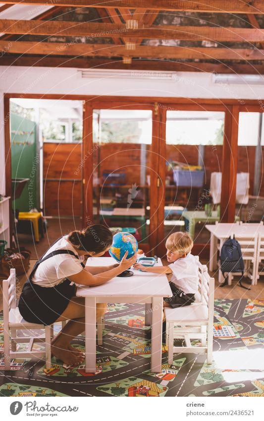 Lehrerin, die dem kleinen Jungen im Vorschulalter bei den Hausaufgaben hilft. Glück schön Ferien & Urlaub & Reisen Stuhl Tisch Kind Schule lernen Mensch Frau