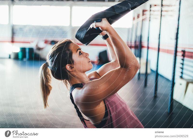 Junge Erwachsene trainierte Frau konzentriert sich auf ihre Bewegung im Fitnessstudio. Lifestyle schön Körper Sport Arbeit & Erwerbstätigkeit Mensch brünett