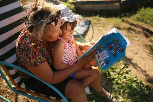 Oma, die einem Kind ein Buch vorliest Lifestyle Freizeit & Hobby Spielen Kinderspiel Kindererziehung Bildung Erwachsenenbildung Kindergarten Schule Schüler