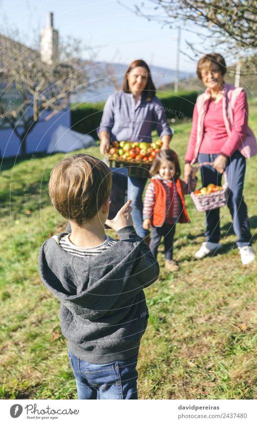 Junge fotografiert Familie mit Äpfeln im Korb Frucht Apfel Lifestyle Freude Glück Freizeit & Hobby Kind Mensch Frau Erwachsene Mann Mutter Großmutter