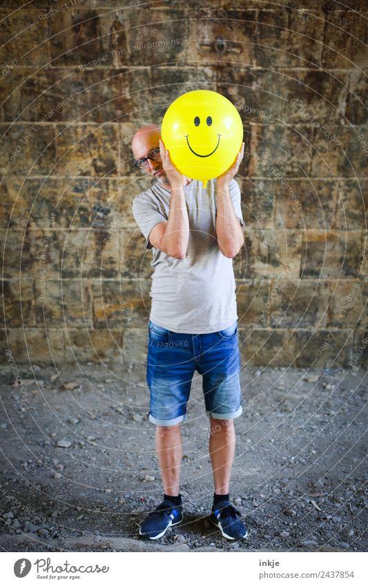 Drittes Bild mit gelbem Smiley Lifestyle Freude Freizeit & Hobby Spielen Mann Erwachsene 1 Mensch 30-45 Jahre 45-60 Jahre Luftballon Zeichen festhalten Lächeln