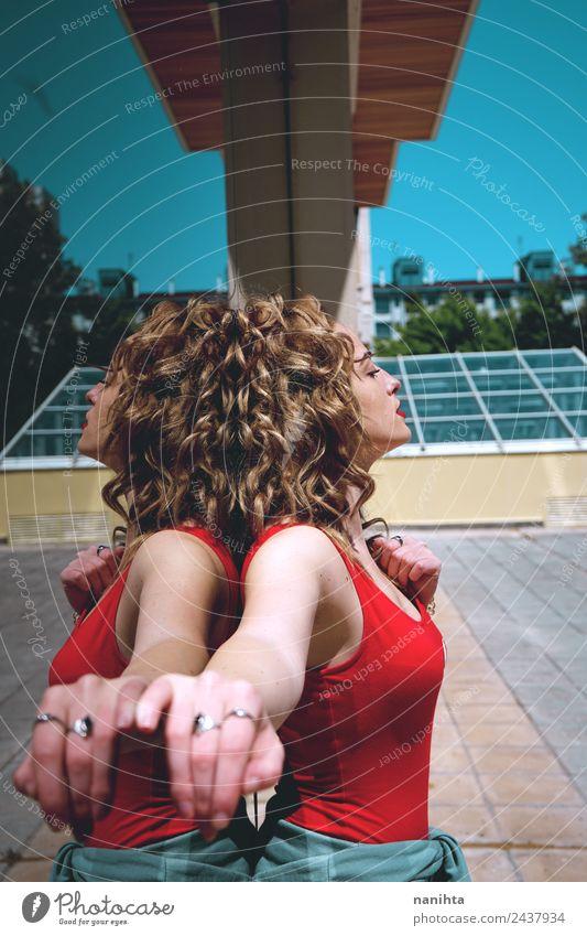 Junge blonde Frau, die sich in einer Spiegelwand auf der Straße spiegelt. Lifestyle elegant Design Haare & Frisuren Haut Wellness harmonisch Mensch feminin