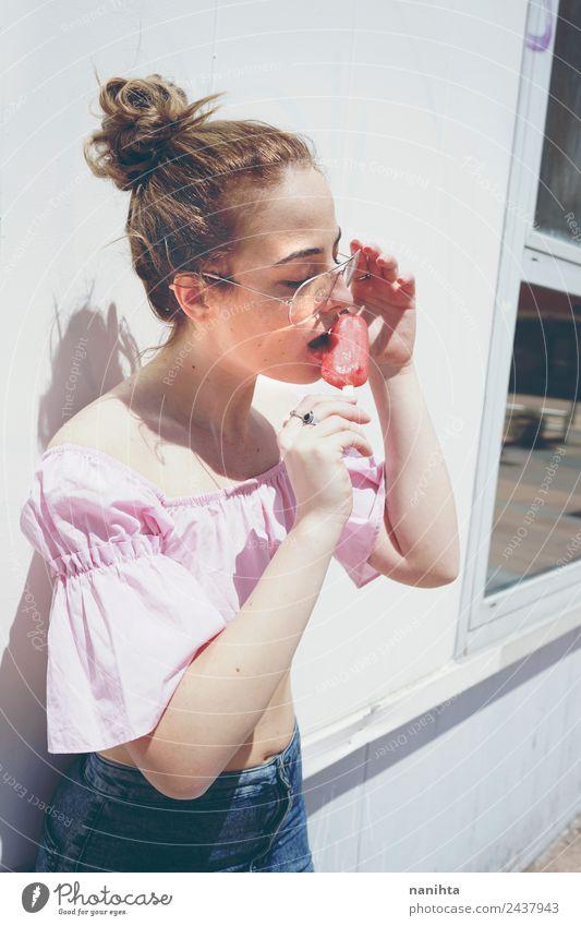 Junge Frau beim Essen eines Eises an einem Sommertag Lebensmittel Speiseeis Ernährung Lifestyle Stil schön Haare & Frisuren Wellness Erholung