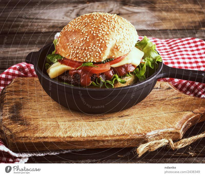 Burger mit einem Fleischklumpen Käse Gemüse Salat Salatbeilage Brot Brötchen Mittagessen Fastfood Pfanne Tisch Holz Essen frisch groß lecker grün schwarz