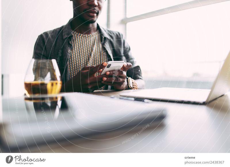 junger afrikanischer Mann, der zu Hause mit Smartphone und Laptop beschäftigt ist. trinken Design Glück Tisch Arbeit & Erwerbstätigkeit Business Telefon PDA