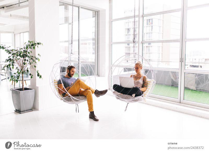 junger Mann und Frau, die nebeneinander im Büro arbeiten. Erholung ruhig Möbel Stuhl Arbeit & Erwerbstätigkeit Beruf Business Unternehmen Computer Notebook
