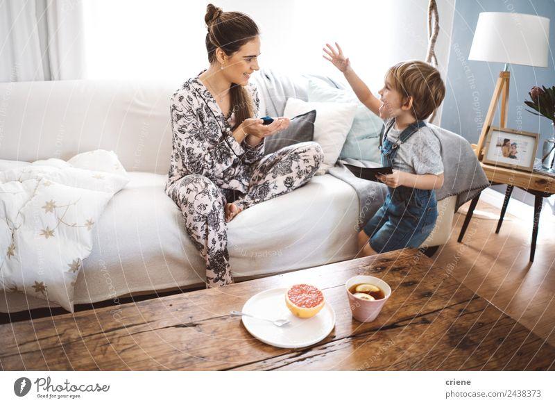 glücklicher kleiner Junge, der der Mutter zu Hause im Wohnzimmer ein Geschenk macht. Frucht Tee Lifestyle Glück schön Leben Erholung Spielen Tisch Kind