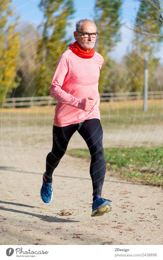 Blick auf den älteren Mann, der durch den Park joggt. Lifestyle Glück Freizeit & Hobby Sport Joggen Mensch maskulin Erwachsene Männlicher Senior 1 60 und älter