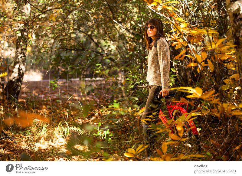 Eine Frau mit einem Fahrrad mitten im Wald. Lifestyle Glück Ferien & Urlaub & Reisen Ausflug Garten Mensch Junge Frau Jugendliche 1 18-30 Jahre Erwachsene Natur