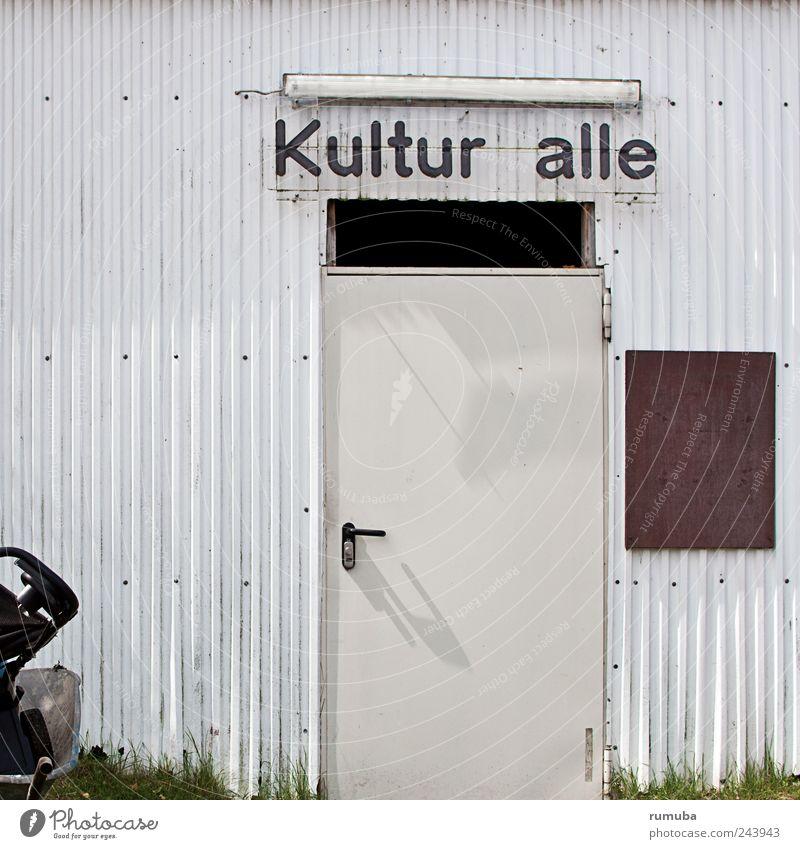 Kultur(f)alle Kunst Ausstellung Mauer Wand Fassade Tür Schriftzeichen trist Kulturhalle Leuchtstoffröhre Schubkarre Wellblech Wellblechhütte Farbfoto