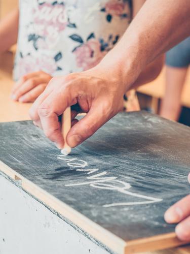Männerhand schreibt mit Kreide Lehrerin auf Tafel Kindererziehung Bildung Schule Schulgebäude Schulkind Schüler Beruf Arbeitsplatz Mensch maskulin feminin Mann