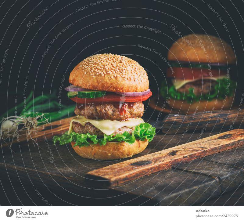 doppelter Cheeseburger Fleisch Käse Gemüse Brot Brötchen Mittagessen Fastfood Tisch Holz Essen frisch groß lecker grün schwarz Burger Hamburger Lebensmittel