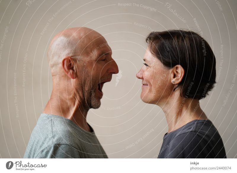 Mann und Frau stehen sich gegenüber. Der Mann öffnet weit den Mund, die Frau grinst. Lifestyle Freizeit & Hobby Erwachsene Freundschaft Paar Partner Leben