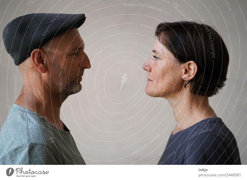Mann und Frau stehen sich gegenüber Zusammensein Zusammenhalt Erwachsene Blick Blick in die Kamera Angesicht zu Angesicht Vor hellem Hintergrund Profil Porträt