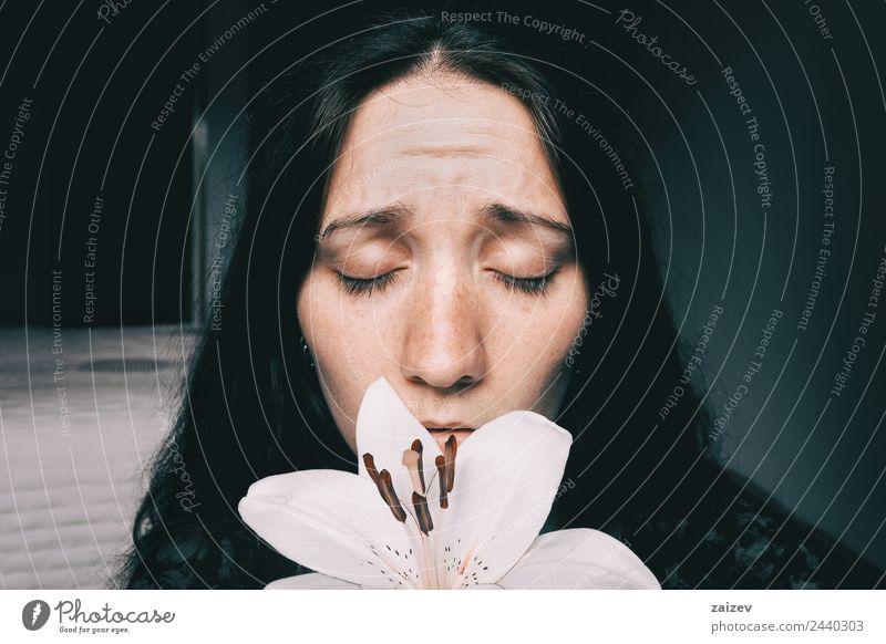 ein Mädchen mit einer weißen Lilie und geschlossenen Augen, besorgt. Lifestyle schön Gesicht Erholung Windstille Mensch feminin Junge Frau Jugendliche