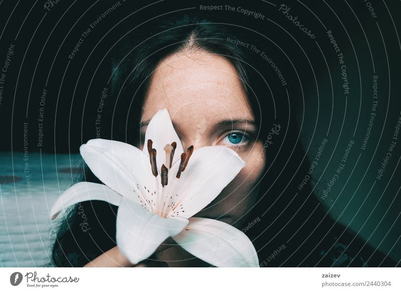ein Mädchen mit einer weißen Lilie, die ein Auge bedeckt. Lifestyle schön Gesicht Erholung ruhig Mensch feminin Junge Frau Jugendliche Erwachsene 1 13-18 Jahre