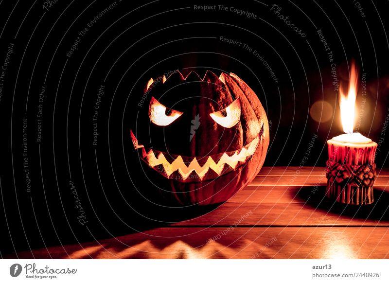 Gruseliger geschnitzter Halloween Kürbis neben brennender Kerze Kopf Auge Mund Kunst Natur Herbst glänzend Lächeln lachen leuchten Aggression alt bedrohlich