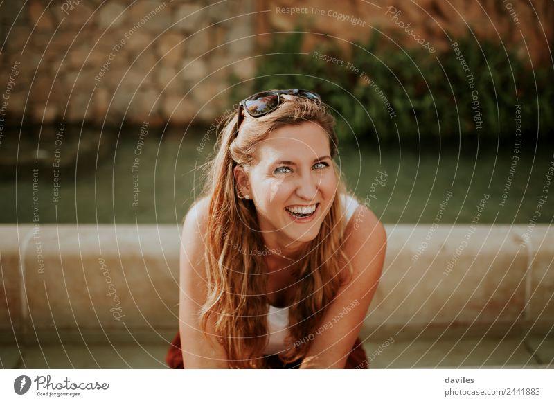Porträt einer jungen blonden Frau, die lachend im Freien in einem Garten sitzt und in die Kamera schaut. Freude schön Gesicht Mensch Junge Frau Jugendliche