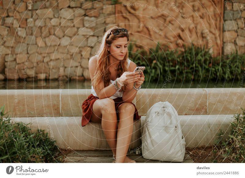 Blondes schickes Mädchen, das ein Smartphone im Freien benutzt. Lifestyle schön Garten Telefon PDA Internet Mensch Junge Frau Jugendliche Erwachsene 1