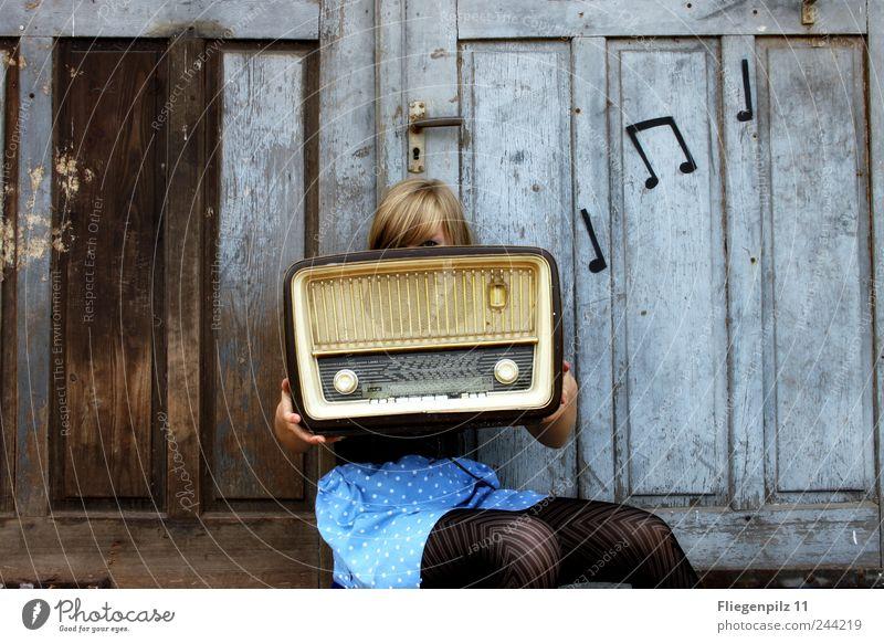 retro gestylte junge Frau posiert mit Radio vor altem Holztor. Musik Noten. Röhrenradio Stil Lautsprecher Radiogerät Junge Frau Jugendliche 1 Mensch Musik hören