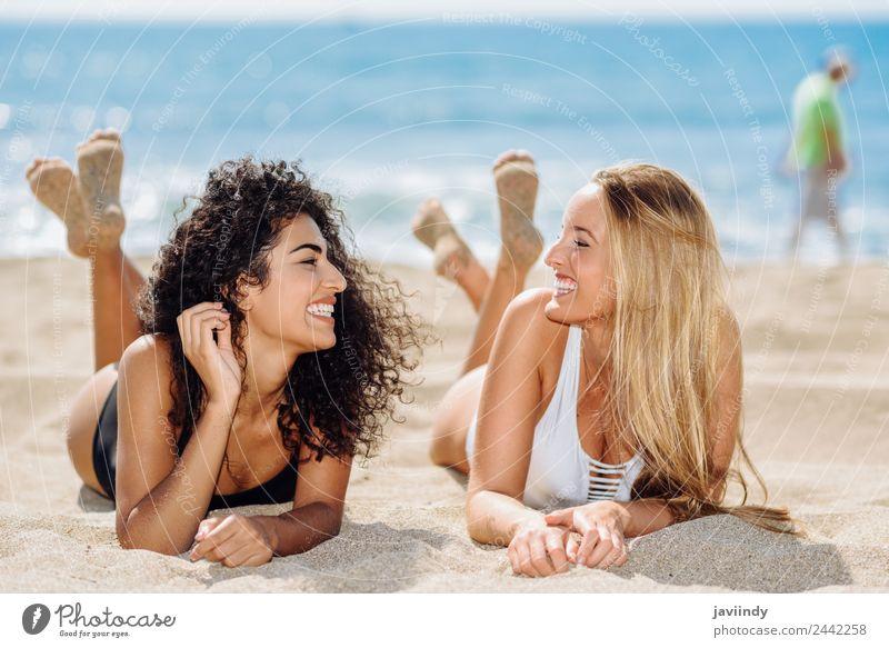 Zwei Frauen, die auf dem Sand am Strand liegen. Lifestyle Freude Haare & Frisuren Ferien & Urlaub & Reisen Sommer feminin Junge Frau Jugendliche Erwachsene