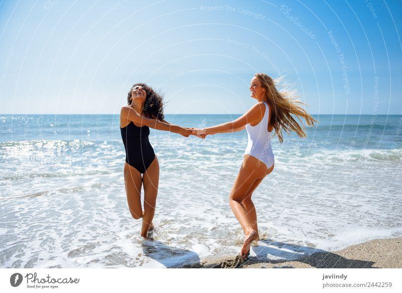 Zwei Frauen mit den Händen am Strand gefangen. Lifestyle Freude Freizeit & Hobby Ferien & Urlaub & Reisen Sommer Mensch feminin Junge Frau Jugendliche