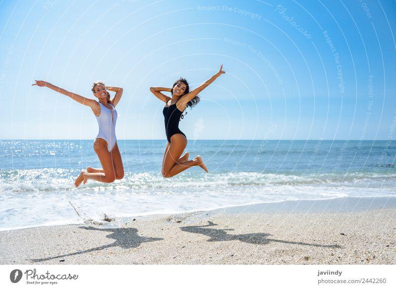Zwei glückliche Mädchen, die an einem tropischen Strand springen. Freude Ferien & Urlaub & Reisen Tourismus Sommer Meer Mensch feminin Junge Frau Jugendliche