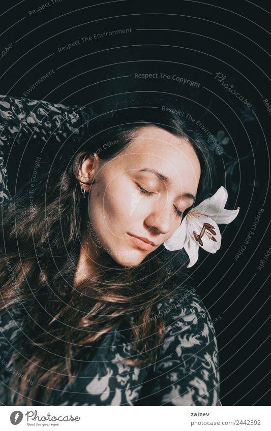 ein Mädchen mit einer weißen Lilie und geschlossenen Augen. Lifestyle schön Gesicht Erholung ruhig Mensch feminin Junge Frau Jugendliche Erwachsene 1