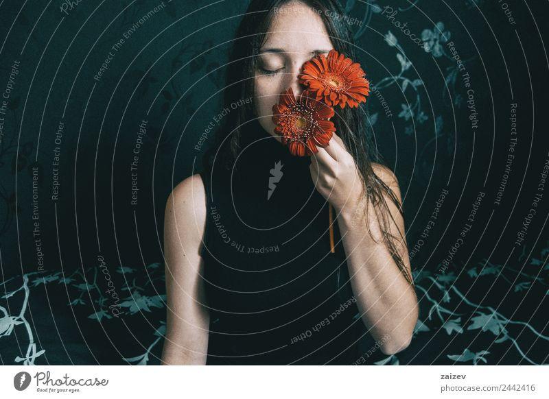ein Mädchen mit blauen Augen und langem Haar, das sich mit einer Gerbera-Blüte bedeckt Lifestyle elegant schön Gesicht Erholung Windstille Mensch feminin
