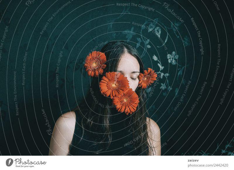ein Mädchen mit blauen Augen und langem Haar, das sich mit einer Gerbera-Blüte bedeckt Lifestyle schön Gesicht Erholung Windstille Mensch feminin Junge Frau