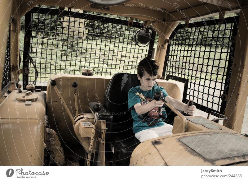 Der Junge in der mächtigen Maschine Baumaschine Mensch Kind 1 8-13 Jahre Kindheit Fahrzeug Baufahrzeug sitzen Spielen gelb Freude Selbstständigkeit fahren