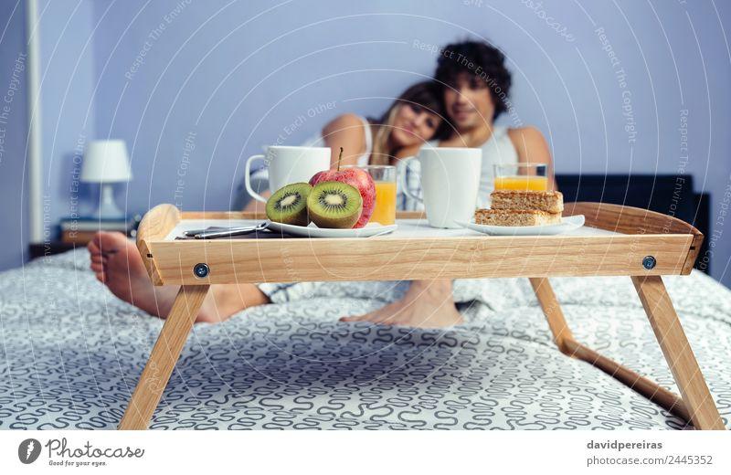 Gesundes Frühstück auf Tablett und im Hintergrund liegendes Paar Frucht Apfel Saft Kaffee Lifestyle Glück schön Erholung Freizeit & Hobby Schlafzimmer Frau