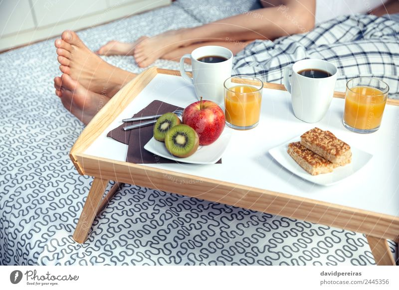 Gesundes Frühstück auf Tablett und Paar Beine im Hintergrund Frucht Apfel Saft Kaffee Lifestyle Glück Erholung Freizeit & Hobby Schlafzimmer Frau Erwachsene