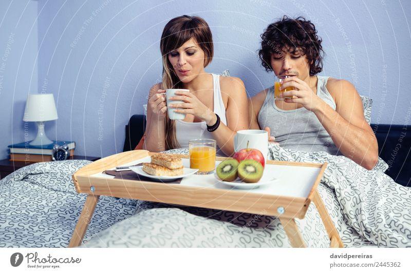 Paar beim Frühstück im Bett, serviert auf dem Tablett. Frucht Apfel Saft Kaffee Lifestyle Glück schön Erholung Freizeit & Hobby Schlafzimmer Frau Erwachsene