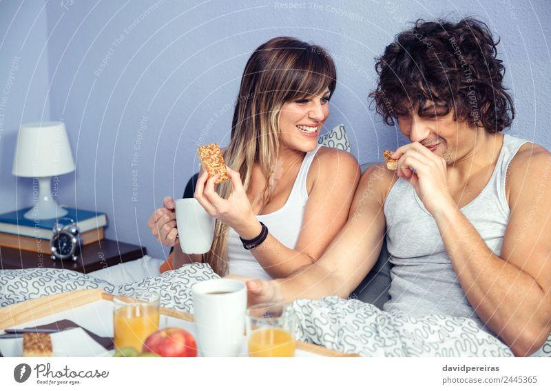 Ein Paar lacht und frühstückt zu Hause im Bett. Frucht Apfel Frühstück Saft Kaffee Lifestyle Glück schön Erholung Freizeit & Hobby Schlafzimmer Frau Erwachsene