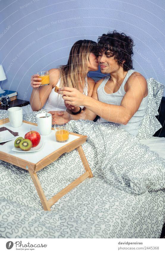 Schöne junge Frau, die sich zu einem Mann im Bett küsst. Frucht Apfel Frühstück Saft Kaffee Lifestyle Glück schön Erholung Freizeit & Hobby Schlafzimmer