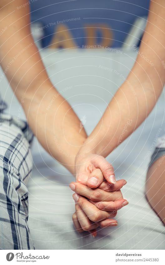 Junges Paar, das Händchen hält und über einem Bett sitzt. Lifestyle Glück schön Erholung Schlafzimmer Frau Erwachsene Mann Familie & Verwandtschaft Hand Liebe