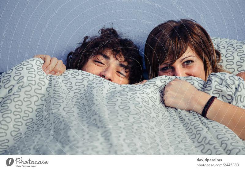 Ein glückliches Paar lacht und deckt die Münder unter der Bettdecke. Lifestyle Glück schön Erholung Schlafzimmer Fotokamera Frau Erwachsene Mann Mund Lächeln