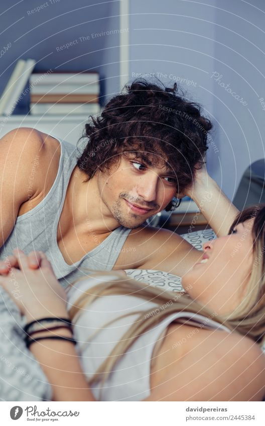 Mann schaut auf eine schöne Frau, die auf dem Bett liegt. Lifestyle Glück Erholung Schlafzimmer Erwachsene Familie & Verwandtschaft Paar Lächeln Liebe schlafen