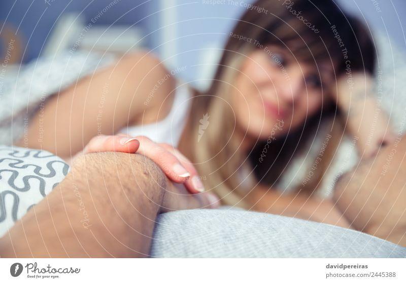 Verliebtes Paar, das Händchen hält und auf dem Bett liegt. Lifestyle Glück schön Erholung Schlafzimmer Frau Erwachsene Mann Hand Lächeln Liebe schlafen