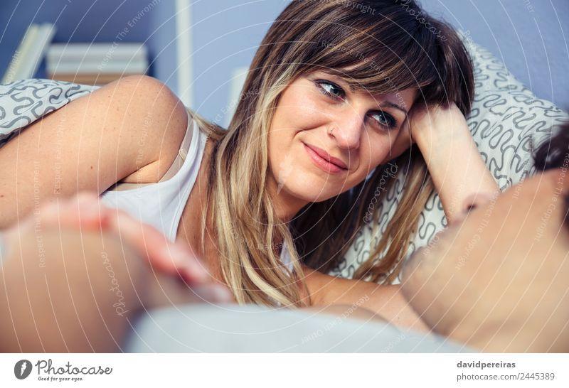 Schöne Frau, die auf den Mann schaut, der auf dem Bett liegt. Lifestyle Glück schön Erholung Schlafzimmer Erwachsene Paar Hand Lächeln Liebe schlafen Sex