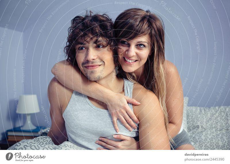 Ein verliebtes Paar, das sich umarmt und lächelt, sitzt über dem Bett. Lifestyle Glück schön Erholung Schlafzimmer Fotokamera Frau Erwachsene Mann